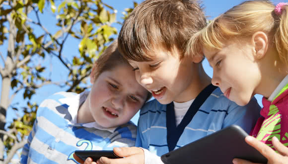Children playing outside with a tablet pc